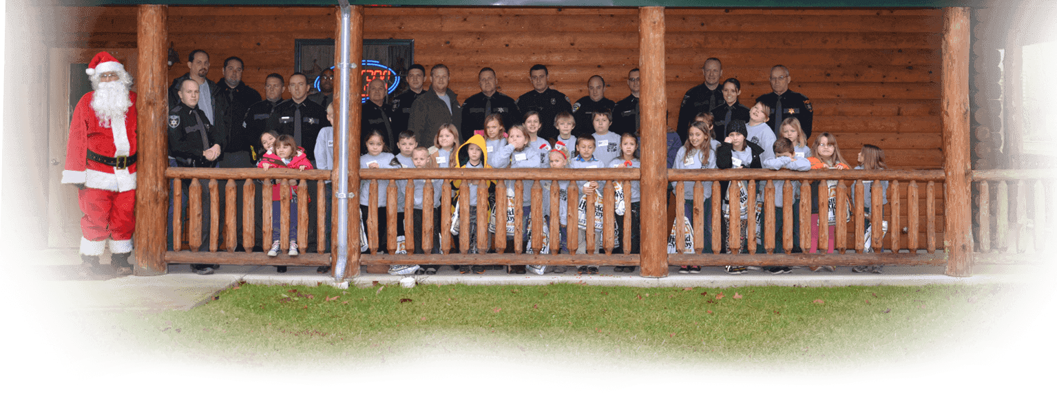 Image of kids and officers standing in front of a log building with santa in frame. The children are all smiling.