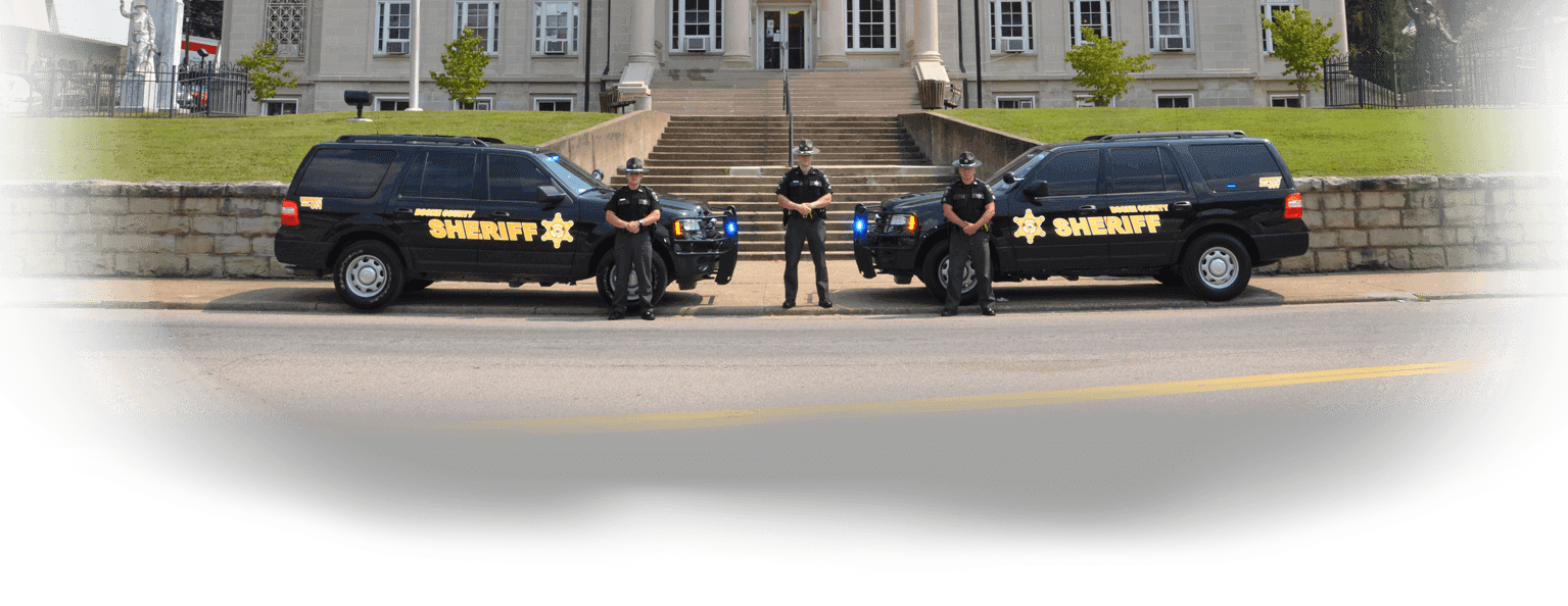 Image of the sheriffs posing in front of the house court with their vehicles.